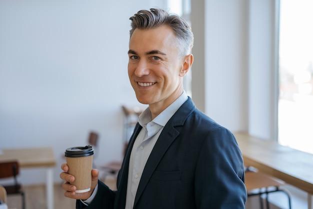 カメラを見て、笑顔でコーヒーのカップを保持しているハンサムな成熟した男の肖像画。コーヒーブレイクのコンセプト