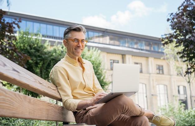 노트북을 사용하는 잘 생긴 성숙한 남자의 초상화입니다. 성공적인 비즈니스