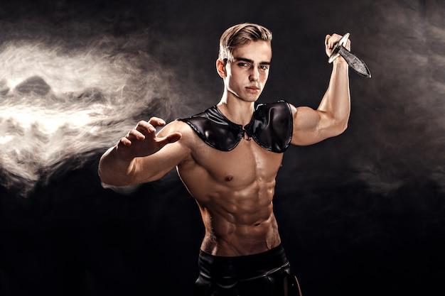 剣でハンサムな筋肉グラディエーターの肖像画。分離されました。スタジオ撮影