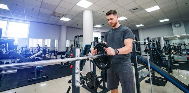 ウェイトディスクとハンサムな筋肉のパワーリフターの肖像画。スポーツジムのバーベルにディスクを置く。閉じる