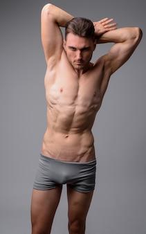 Портрет красивого мускулистого мужчины без рубашки на сером
