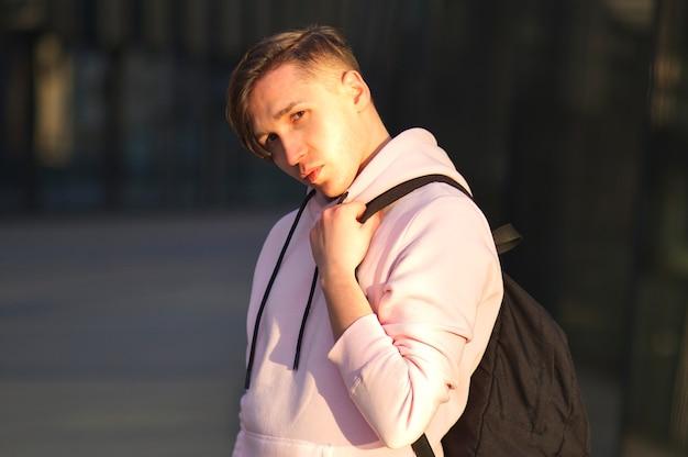 Портрет красивого симпатичного парня с длинными волосами, молодого симпатичного человека, студента университета или колледжа в