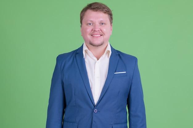 크로마 키 또는 녹색 벽에 양복을 입고 잘 생긴 과체중 수염 사업가의 초상화