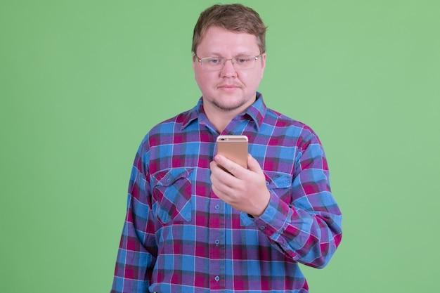 クロマキーまたは緑の壁に眼鏡をかけたハンサムな太りすぎのひげを生やしたヒップスターの男の肖像画