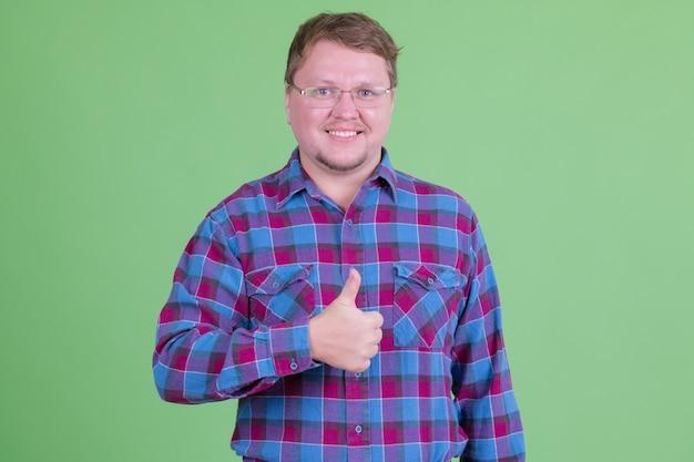 크로마 키 또는 녹색 벽에 안경 잘 생긴 과체중 수염 힙 스터 남자의 초상화