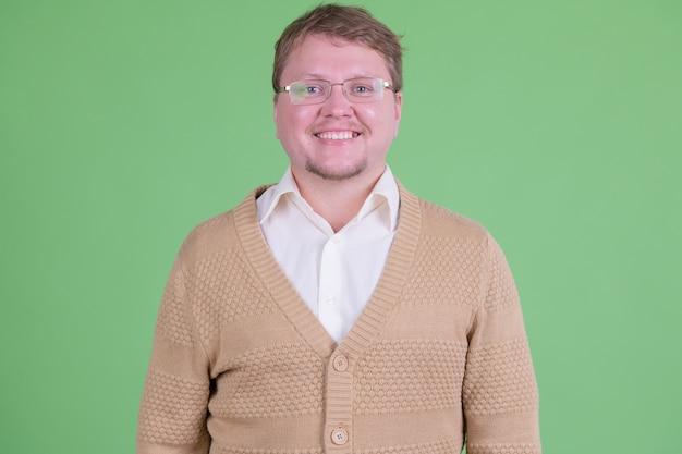 크로마 키 또는 녹색 벽에 안경을 가진 잘 생긴 과체중 수염 난 남자의 초상화