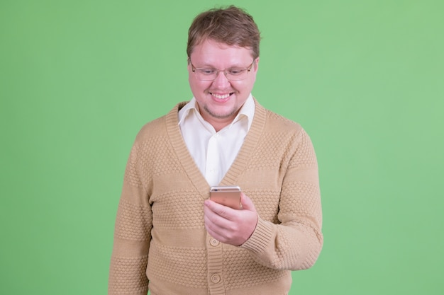 Портрет красивого полного бородатого мужчины в очках на фоне цветного ключа или зеленой стены
