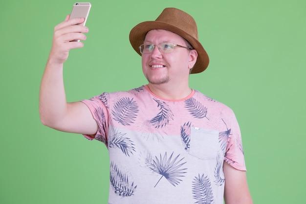 크로마 키 또는 녹색 벽에 잘 생긴 과체중 수염 관광 남자의 초상화