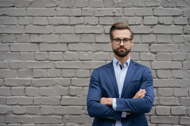 Портрет красивого задумчивого бизнесмена со скрещенными руками, смотрящего на копировальное пространство камеры