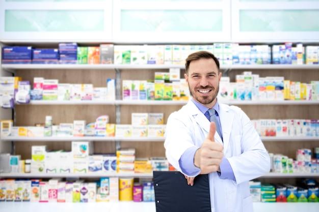 Портрет красивого фармацевта, держащего палец вверх в аптеке с полкой, полной лекарств