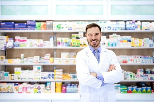 Портрет красивого фармацевта, стоящего со скрещенными руками в аптеке с полкой, полной лекарств