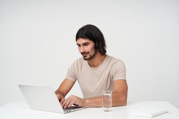검은 긴 머리와 수염을 가진 잘 생기고 긍정적 인 사업가의 초상화. 사무실 개념. 랩톱에서 작업하는 데 집중했습니다. 흰색 책상에 앉아. 직장, 흰 벽 위에 절연