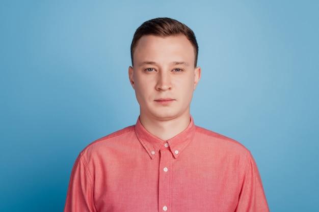 青い背景の上のハンサムなポジティブクールな男の外観カメラの肖像画
