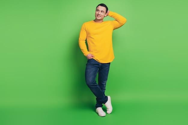 緑の背景にハンサムなポジティブな男の手のポケットタッチヘッドの肖像画