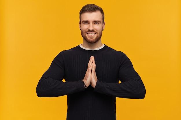 ブルネットの髪とひげを持つハンサムでポジティブな男性の肖像画。ピアスあり。黒のセーターを着ています。黄色の壁に隔離されたナマステジェスチャーを表示
