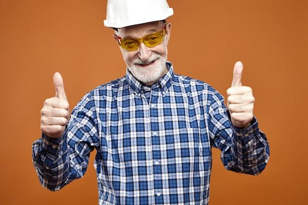 안전모와 노란색 안경에 잘 생긴 긍정적 인 수석 감독의 초상화는 엄지 손가락 제스처를 표시하고 행복하게 웃으며 좋은 일을 위해 그의 작업 승무원을 격려합니다. 건설 및 개조