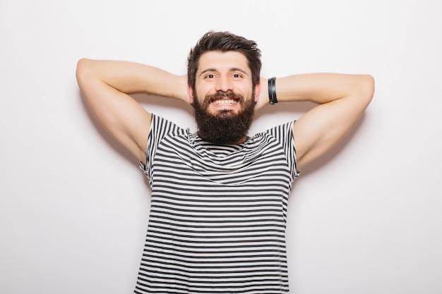 회색 벽에 고립 된 잘 생긴 긍정적 인 젊은 남자의 초상화