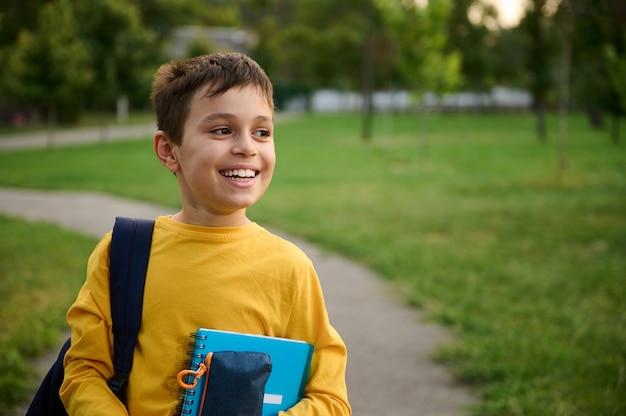 バックパックとワークブックを手にしたペンシルケースを持ったハンサムな思春期前の男子生徒の肖像画、目をそらし、歯を見せる笑顔で笑って、学校での初日後のレクリエーションを楽しんでいます