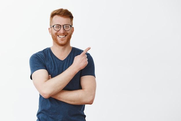 眼鏡とtシャツの剛毛を持つハンサムな赤毛の男性の肖像画、右上隅を指して、嬉しそうに笑う