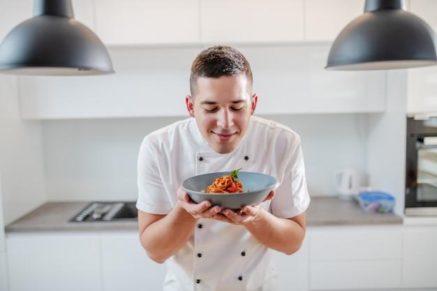 ハンサムな満足している白人のシェフの肖像画は、キッチンで制服立って、プレートに新鮮なタリアテッレの臭いがします。イタリア料理。