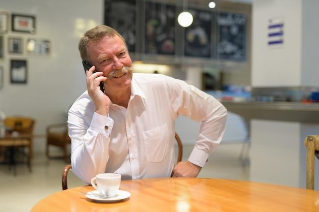 Портрет красивого старшего бизнесмена с усами в кафе