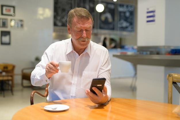 コーヒーショップで口ひげを持つハンサムなシニアビジネスマンの肖像画