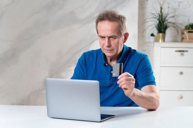신용 은행 카드 지불을 들고 노트북 컴퓨터와 잘 생긴 수석 노인 은퇴 한 남자의 초상화