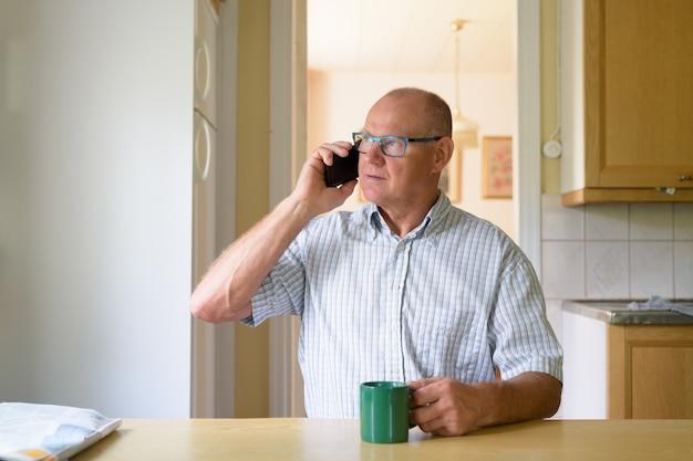 Портрет красивого старшего мужчины, расслабляющегося дома