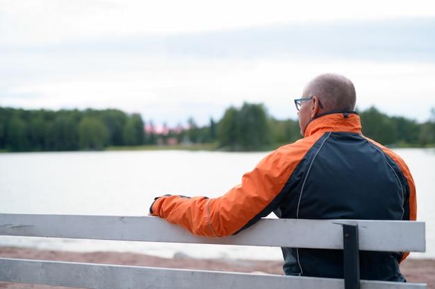 호수보기에 벤치에 앉아 잘 생긴 수석 남자의 초상화