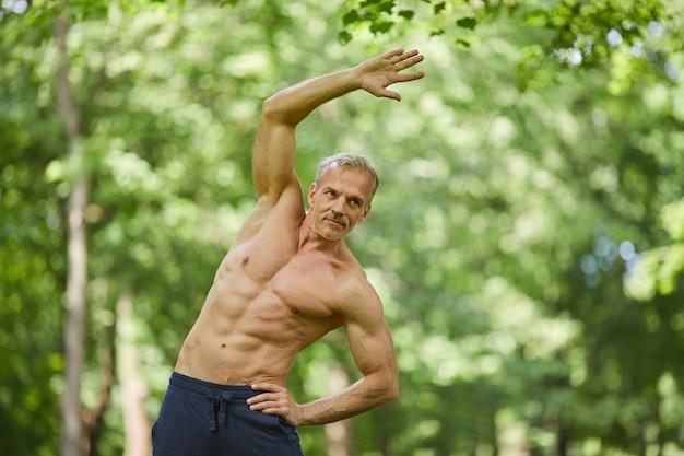 스트레칭 운동을 하 고 공원에서 어딘가에 토플리스 서 잘 근육질 몸매를 가진 잘 생긴 수석 운동가의 초상화