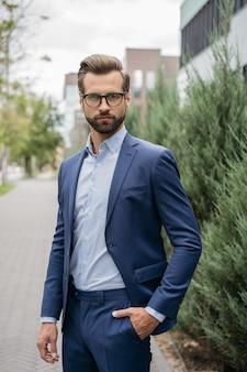 Портрет красивого серьезного делового человека в костюме и стильных очках, смотрящего в камеру