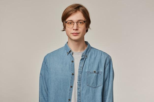 금발 머리를 가진 잘 생기고, 심각한 남자의 초상화. 데님 셔츠와 안경 착용. 사람과 감정 개념. 회색 벽에 고립 된 자신감을보고