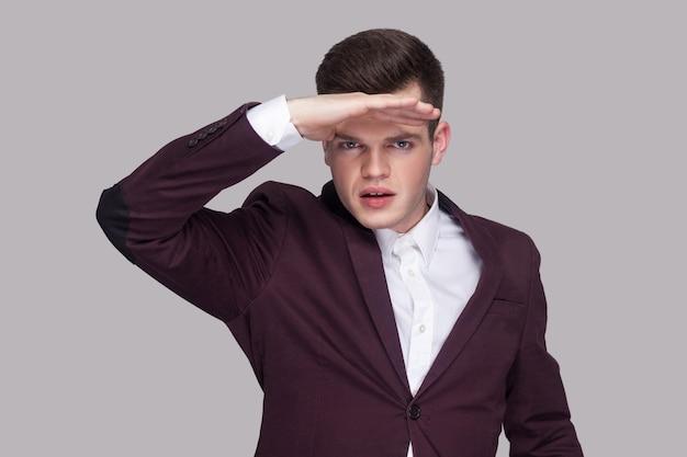Портрет красивого серьезного молодого человека в фиолетовом костюме и белой рубашке, стоящего, смотрящего далеко и держащего руку на лбу. крытая студия выстрел, изолированные на сером фоне.