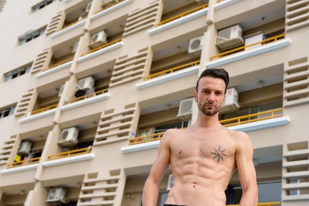 Портрет красивого мужчины без рубашки на открытом воздухе с шестью пакетами пресса и татуировками