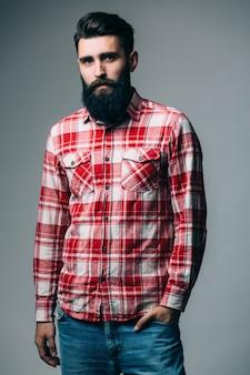 Портрет красивого одинокого бородатого молодого человека с серьезным выражением лица над серой стеной с копией пространства