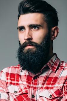 コピースペースと灰色の壁に真剣な表情でハンサムな単一のひげを生やした若い男の肖像画