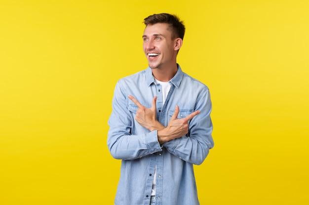 Портрет красивого улыбающегося белокурого человека в повседневной одежде, смеющегося и смотрящего влево, указывая в сторону. веселый покупатель-мужчина делает покупки в магазине, выбирая один из двух вариантов.