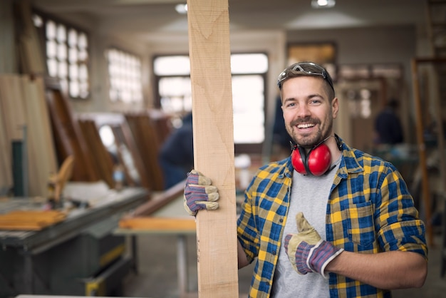 Портрет красивого улыбающегося плотника с деревянным материалом в мастерской, держащего палец вверх
