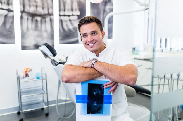 彼の患者のx線画像を保持しているハンサムな笑顔の歯科医の肖像画。