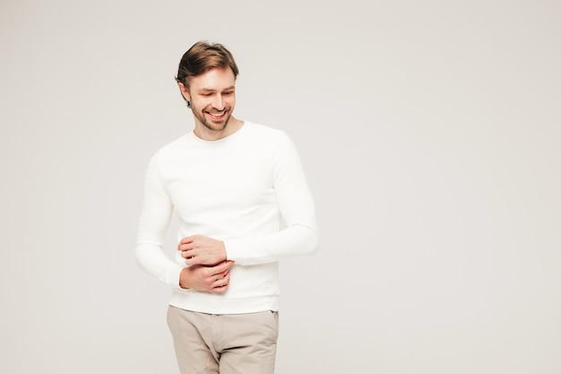 Портрет красивого улыбающегося хипстера-лесоруба модели бизнесмена в повседневном белом свитере и брюках