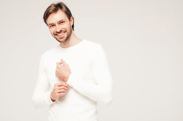 カジュアルな白いセーターとズボンを身に着けているハンサムな笑顔の流行に敏感な腰痛のビジネスマンモデルの肖像画