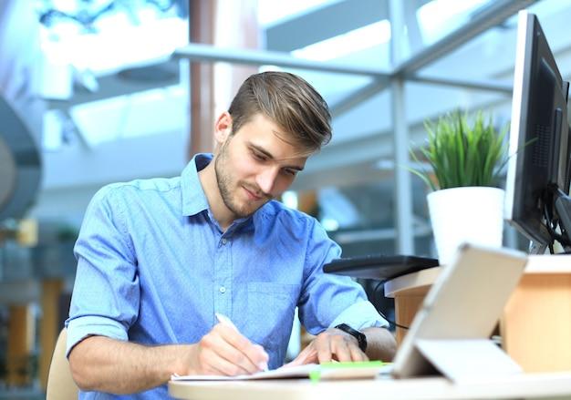 직장에서 메모를 하는 캐주얼 셔츠에 잘생긴 웃는 남자의 초상화
