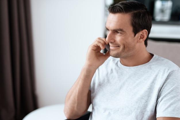 電話を話しているハンサムな笑顔の人の肖像画。