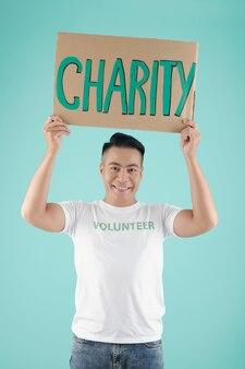 Портрет красивого улыбающегося молодого азиатского человека, держащего плакат с благотворительной надписью и смотрящего в камеру