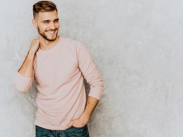Портрет красивый улыбающийся молодой человек модели носить повседневные летние розовые одежды. мода стильный мужчина позирует