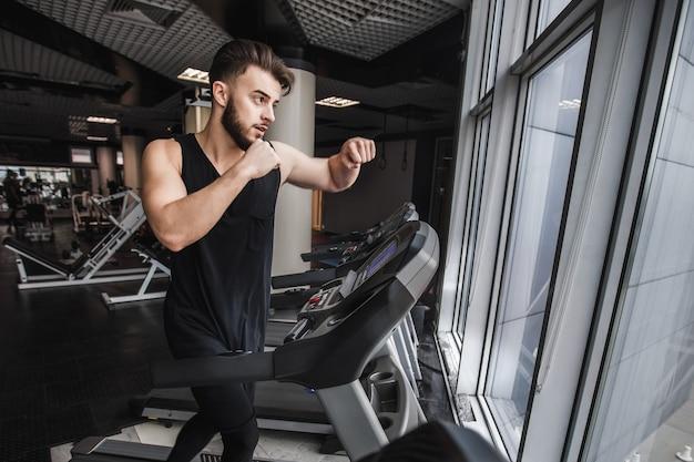 Портрет красивого спортсмена, делающего кардио-тренировки и упражнения по боксу на стационарной беговой дорожке в тренажерном зале