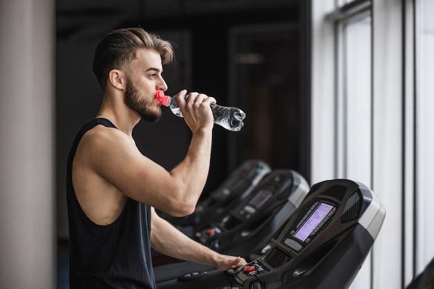 Портрет красивого спортсмена, делающего кардио тренировки и питьевой воды в тренажерном зале