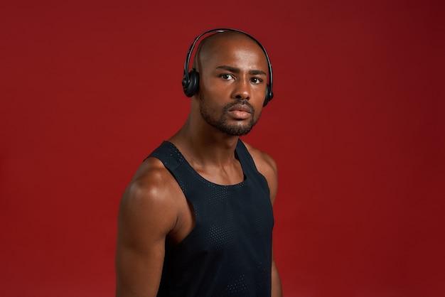 Портрет красивого спортивного афроамериканца в наушниках, смотрящего в камеру, стоя против