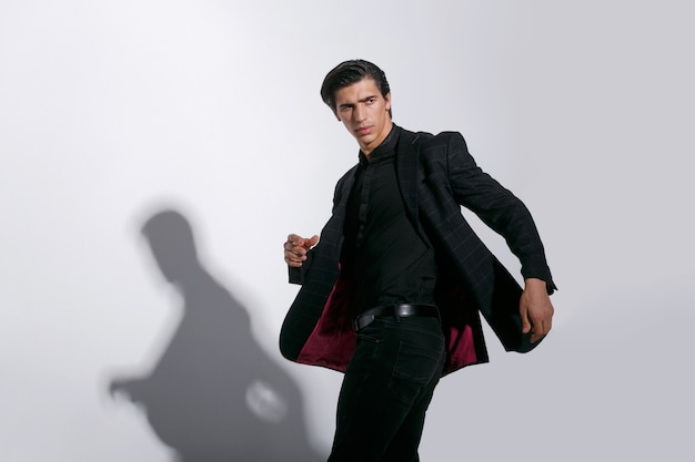 白い背景で隔離の黒のスタイリッシュなスーツのハンサムな強い若い男の肖像画。水平方向のビュー。