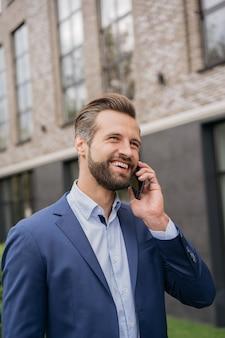 Портрет красивого бизнесмена, говорящего по мобильному телефону, идущего по городской улице